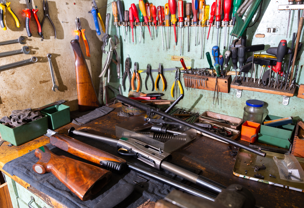 Workplace of gunsmith in weapons workshop with tools and disassembled shotgun